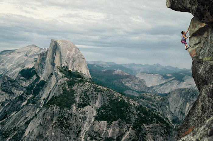 Adventure photography of a woman rock climbing in a vast mountainous landscape by Andy Bardon.