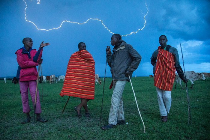 Night photography of 4 African men standing outdoors with lightning striking in the background