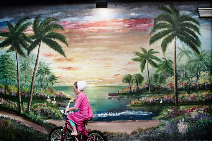 Photo of a girl riding a bike past a painted landscape by Dina Litovsky. Famous photographers to follow.