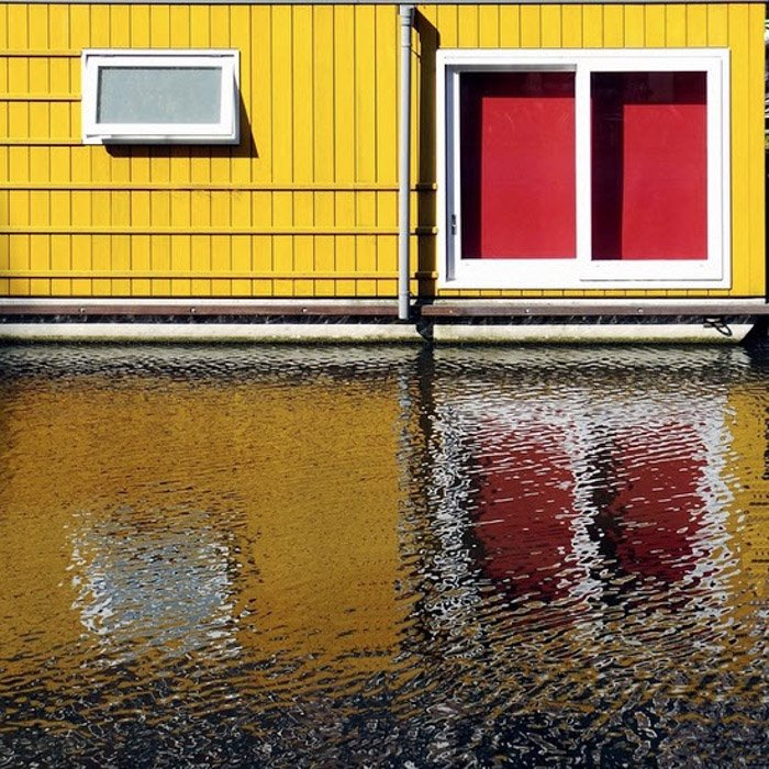 Photo of a yellow house with red windows reflected in the water below