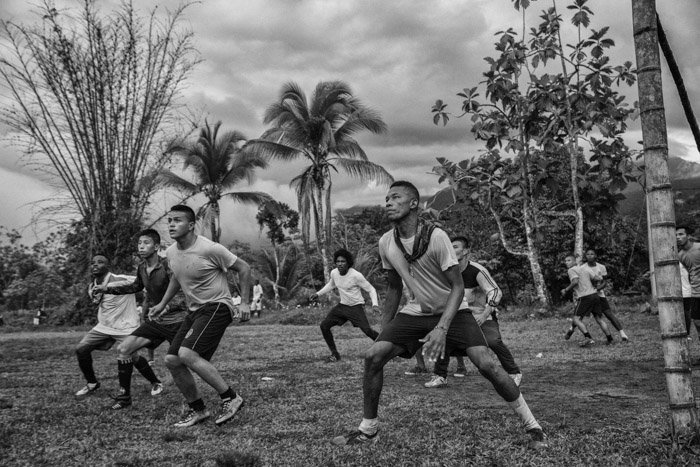 Black and white photography of men playing soccer in Cambodia by Juan Arredondo.