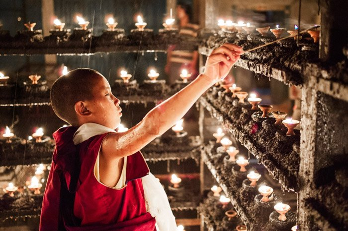 Martin Edstrom travel photography of a young boy lighting a candle. Famous photographers to follow online