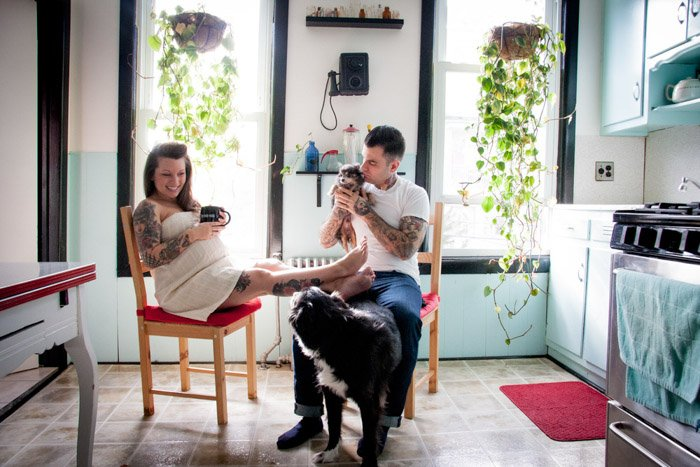 Photo of a couple with 2 dogs relaxing in the kitchen by Nina Robinson