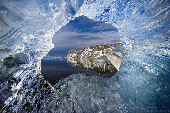 A seascape photographed through a hole in ice by Paul Nicklen.