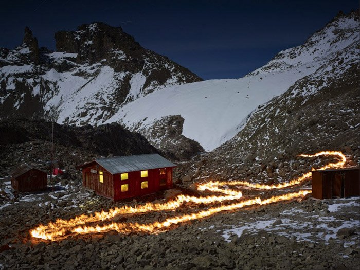 Photo of a firetrail by a woodenhouse in a snowy mountainous landscape by Simon Norfolk.