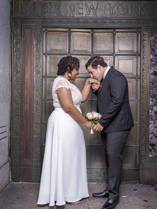 Wedding photography of newlywed couple holding hands outside a doorway by Wayne Lawrence.