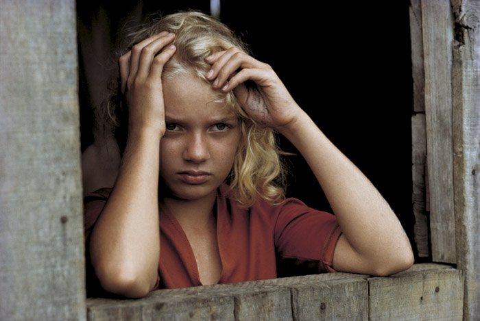 Portrait of a little girl looking through a door frame by William Albert Allard..
