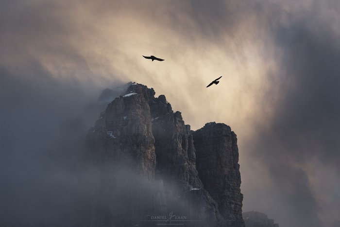 An eerie and dramatic fine art landscape photography shot of a rocky mountain being circled by birds and a stormy overcast sky.