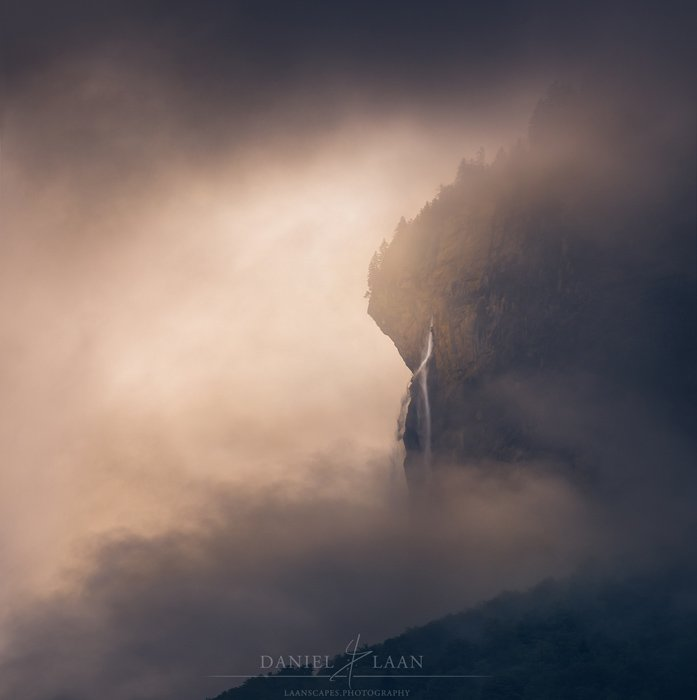 An eerie and dramatic fine art landscape photography shot of a rocky mountain surrounded by a stormy overcast sky.