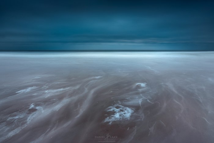 An dramatic fine art landscape photography shot of the seashore leading to a stormy sky.