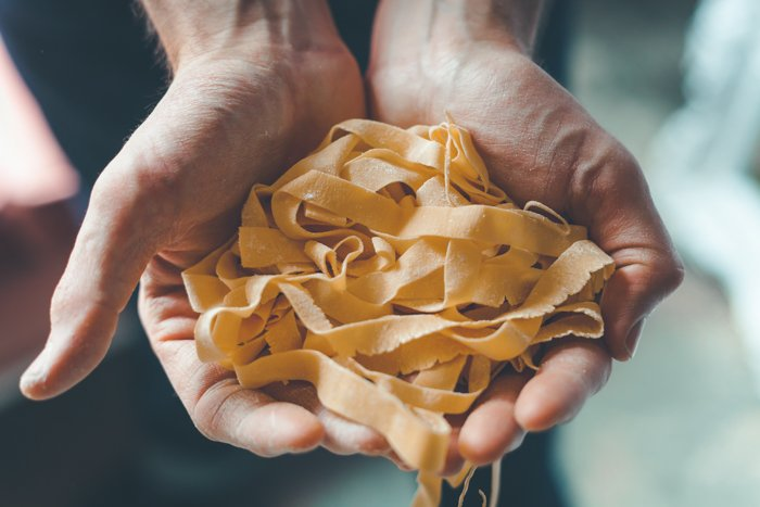 Food photography of hands holding fresh pasta.