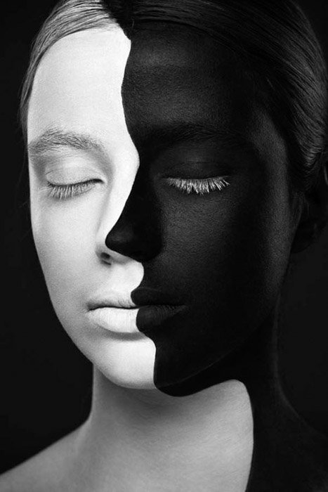 A portrait of a womans face painted half black and half white on a black backgrounds as an example of colours juxtaposition.