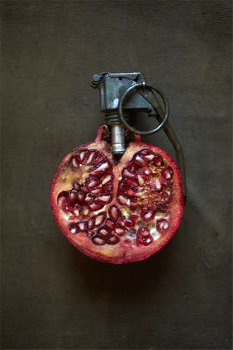 Giuseppe Colarusso still life juxtaposition photography of a pomegranate with grenade pin . Photography juxtaposition examples.