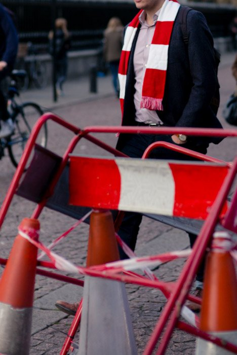 Street photography of a man wearing a scarf that resembles the environment in the road work barriers and tape.