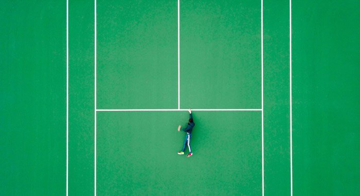 Overhead photo of a man on a tennis court but looks as though he is holding onto a ledge for dear life