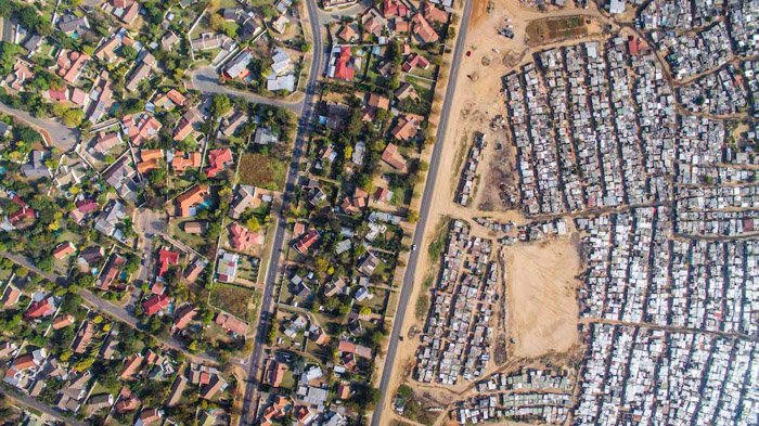 Johnny Miller aerial photography of a densely populated area vs the sparser, and greener area to the left