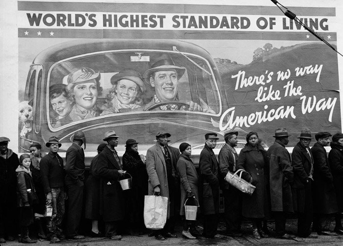 Black and white photo of many people queuing for food in the foreground juxtaposed with a billboard stating 'world's highest standard of living'. juxtaposition examples
