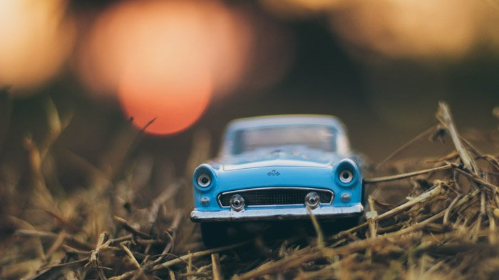 A photo of a toy blue car on grass
