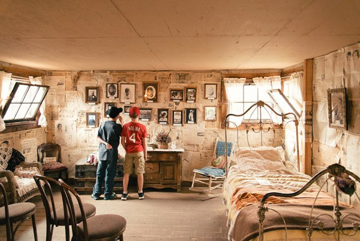 A photo of two boys in an old fashioned bedrhotos on the wall.