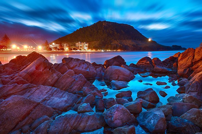 A stunningly coloured photograph of a rocky foreground with a mountain and dramatically lit night sky in the background. Using the foreground for landscape photography composition