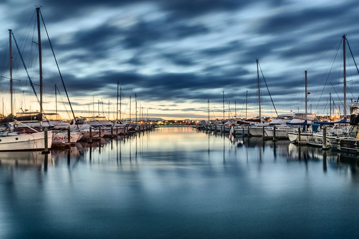 A photo of boats lined up in the harbour beneath a dramatic cloudy sky. Symmetry in landscape photography composition