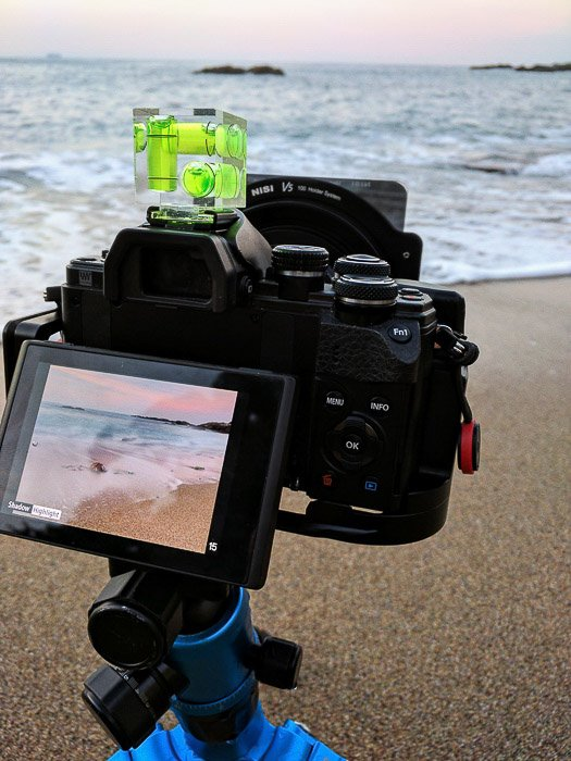 Image of a camera on tripod with an old fashioned bubble level for long exposure photography