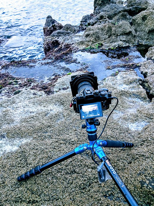 Image of a camera and tripod set up on coastal rocks for long exposure photography.