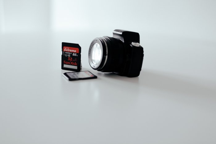 Image of a camera and memory card on a white background.