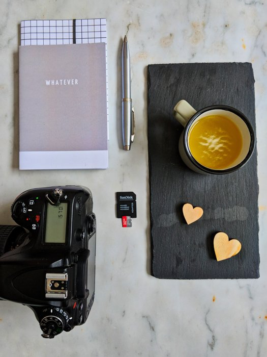 Overhead still life photography shot of a camera, notebook, pen, coffee cup and memory card