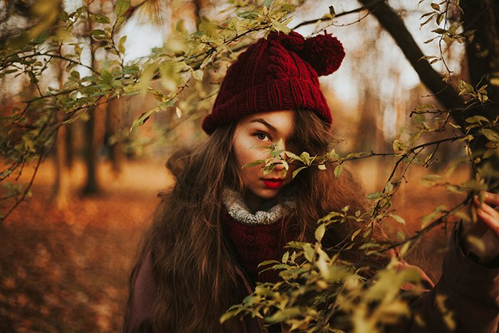 portrait of a girl in red hat looking through trees on a beautiful autumn day - natural light portraits