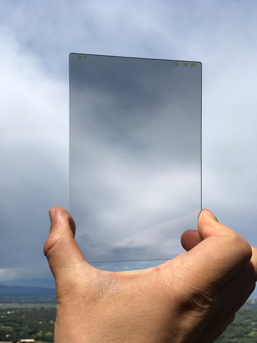 Close up photo of a hand holding a graduated neutral density filter to the sky