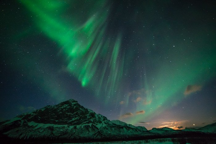 Stunning landscape with northern lights and starry sky above a mountain.