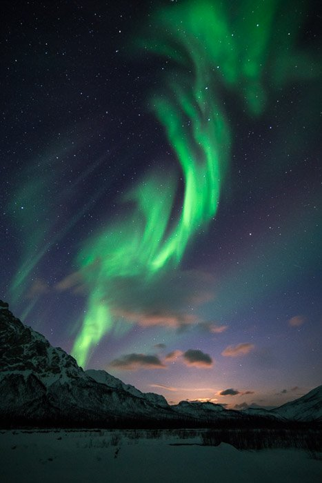 Photograph of the northern lights in Alaska with an icy mountain landscape below.