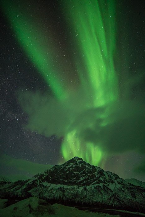 Photograph of the northern lights in Alaska with an icy mountain in the foreground