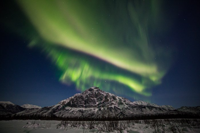Photograph of the northern lights above a snowy mountain.