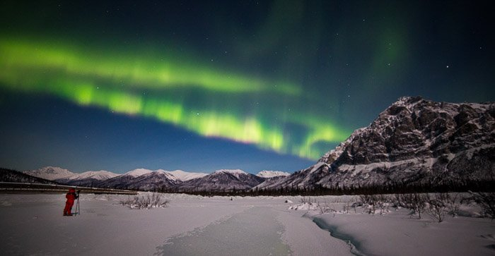 A mountain scene with a photographer during an aurora borealis photography workshop