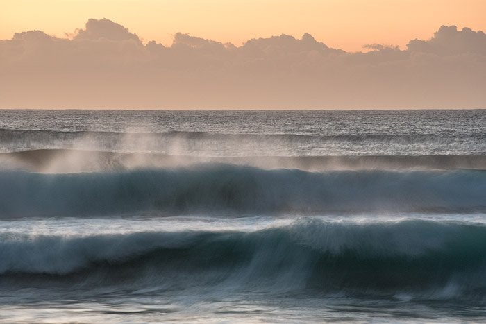 Blurred waves seascape with orange and yellow sky.
