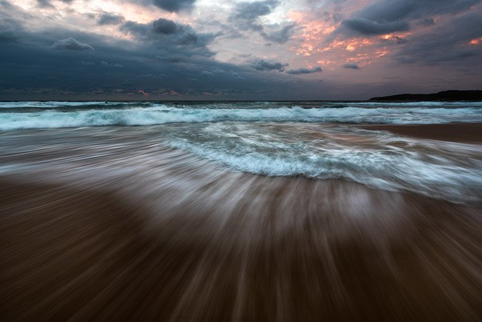 Impressive reducing wave seascape with fiery sunset sky using shutter speed of 0.5 - 2 seconds.