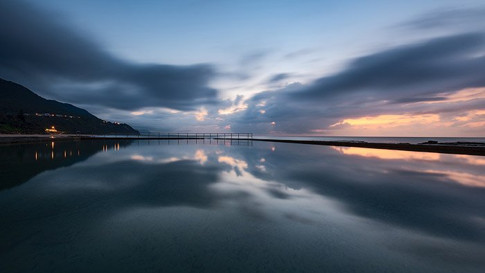 Calm evening seascape with sunset sky and mountains reflected in the sea.