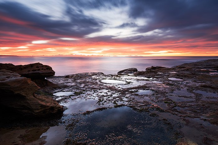 A dramatically lit rock pool seascape with fiery sunset.