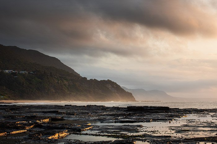 Calm evening seascape with overcast sky and mountains.