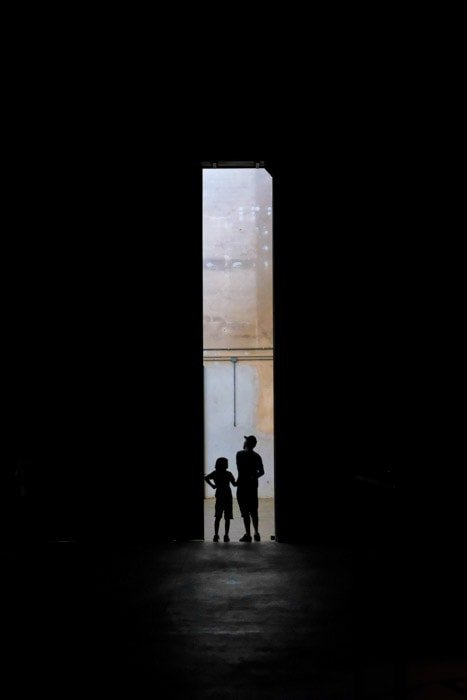 An essay photo of the silhouettes of a man and child standing in a dark doorway.
