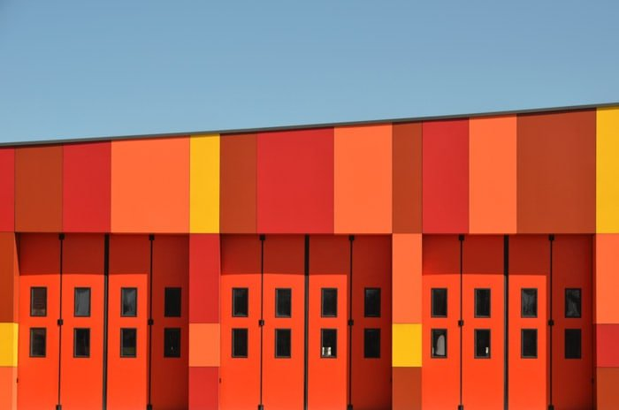 Photo essay examples of a bright red and orange building under blue sky.