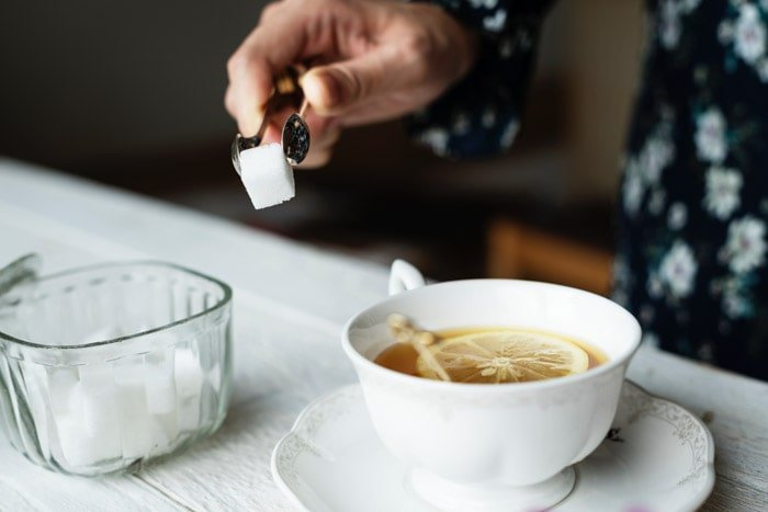 Photo essay detail of someone placing a sugar cube into a cup of tea.