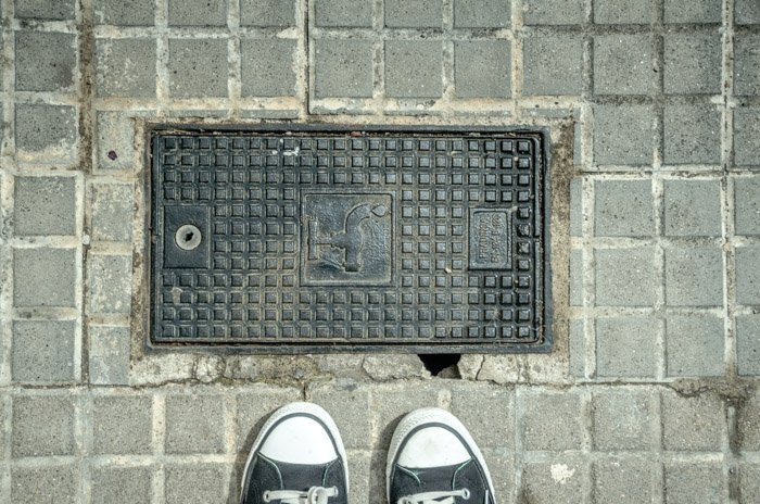 An overhead photo of a pair of shoes on concrete. Photo walk tips.