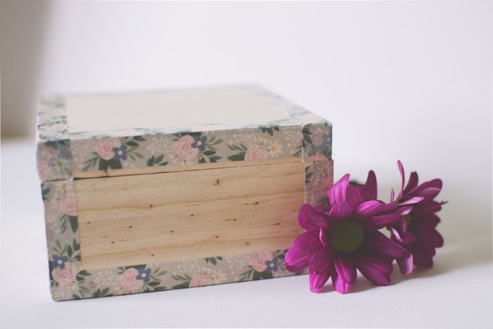 A close up of a wooden box beside purple flowers. Photography ideas.