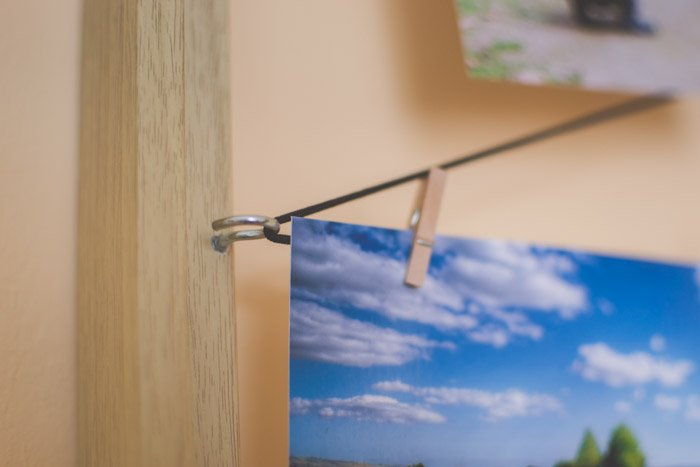 A photograph of a landscape hanging by small wooden pegs on the wall. creative photography ideas.