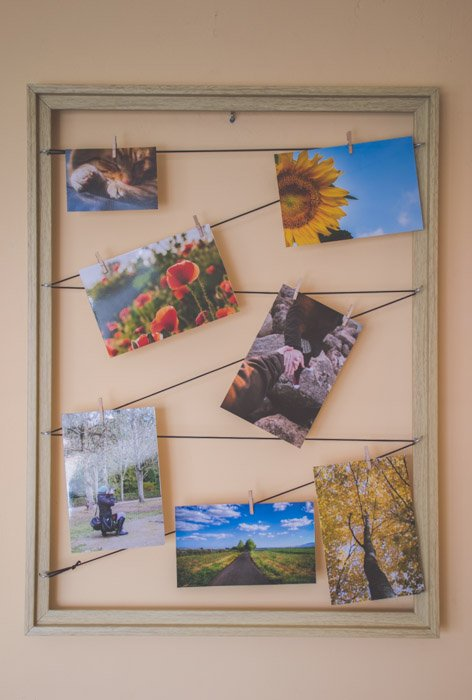 A unique photo gift make from a wooden frame with 7 photographs hanging on strings inside. A painted wooden clothes hanger on the wall. Creative photography ideas.