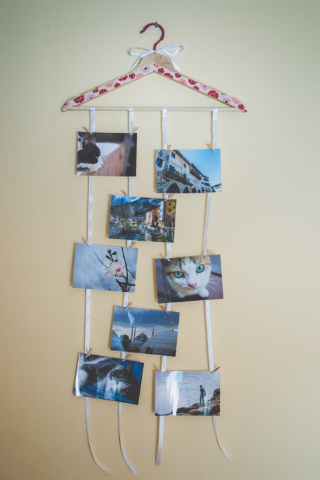 A painted wooden clothes hanger on the wall holding 8 unique photo gifts. Creative photography ideas.