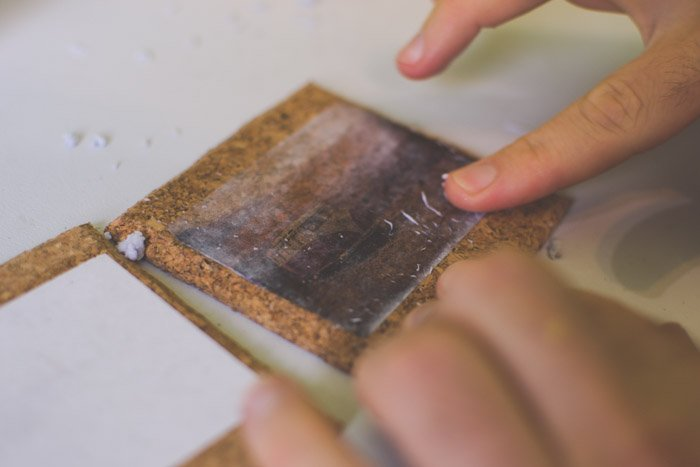 A close up photo of sticking photographs to coasters. Creative photography ideas.